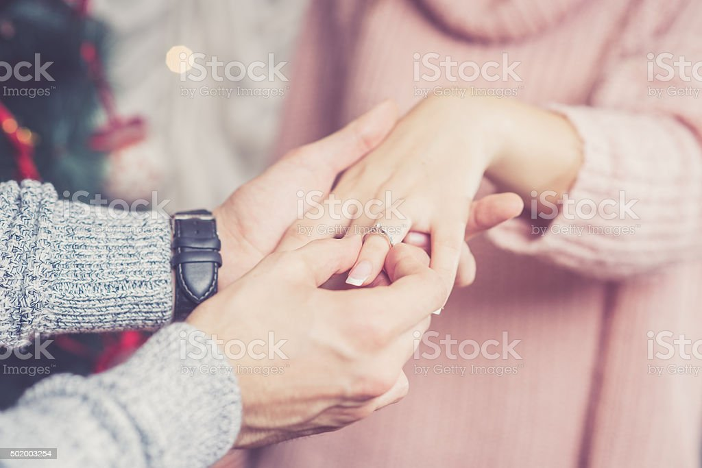 Young man proposing to his girlfriend stock photo