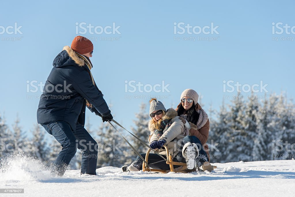 Young man pulling girls on winter snow sledge stock photo