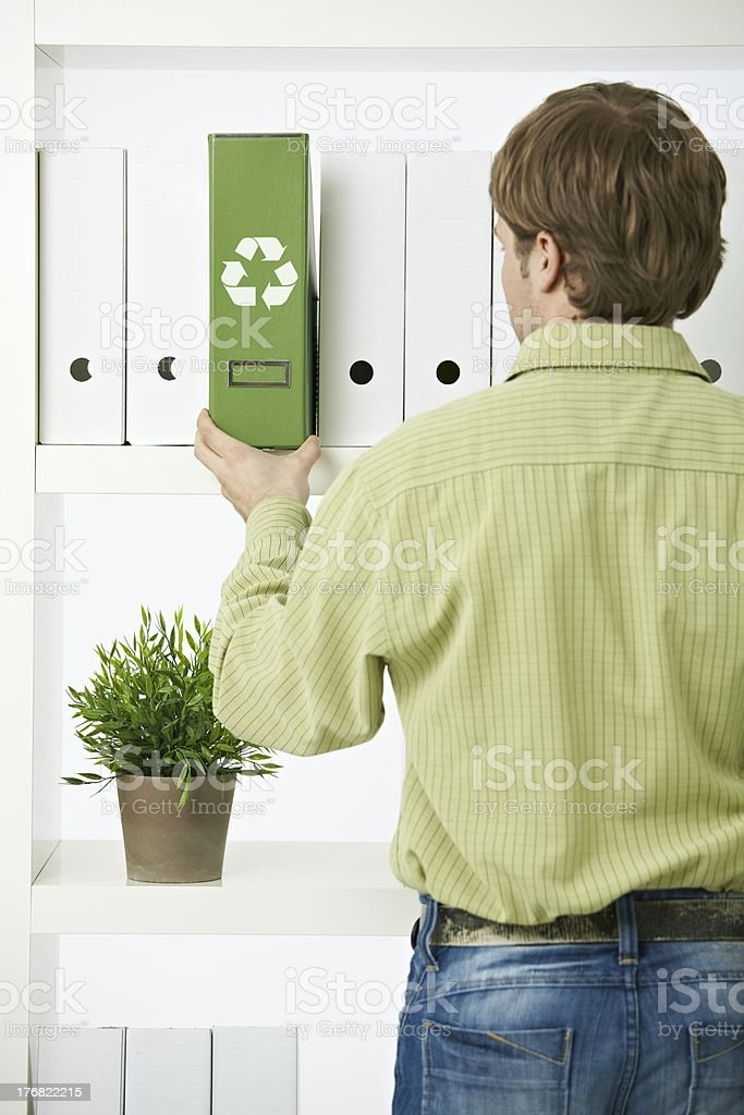 Young man pulling out green folder royalty-free stock photo