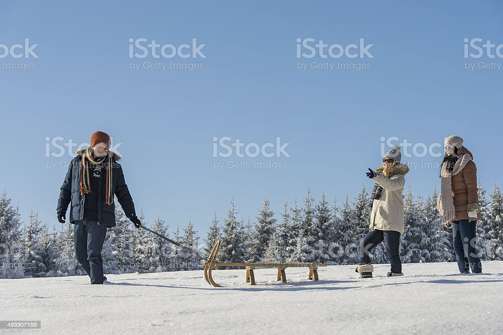 Young man pulling snow sledge winter countryside stock photo