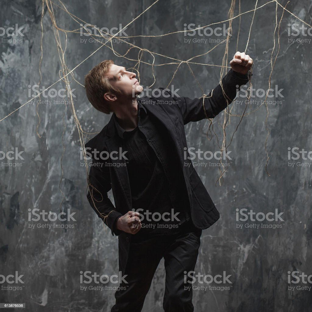 Young man pulling something behind him. Concept of manipulation and stock photo