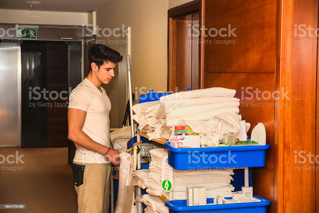 Young man pushing a housekeeping cart in hotel stock photo