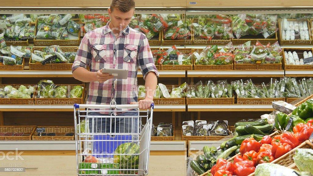 Young man pushing cart along the grocery aisles in the foto de stock libre de derechos