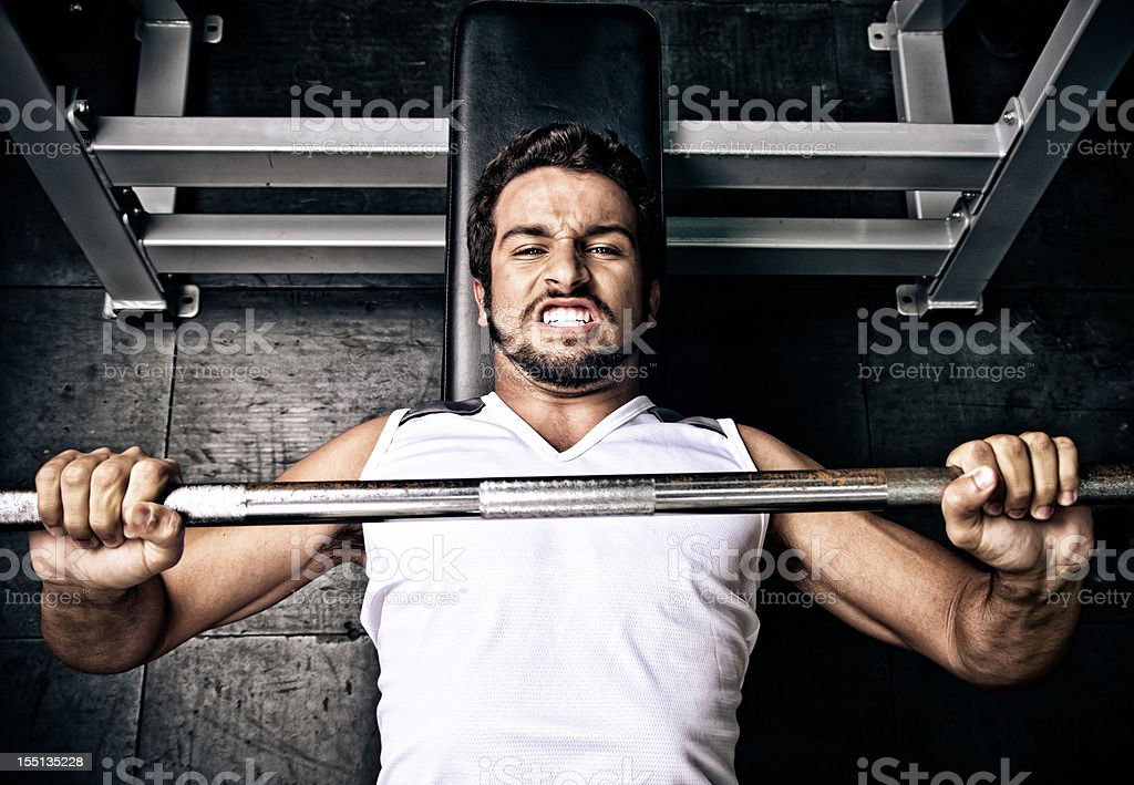 Young man putting effort in on a bench press stock photo