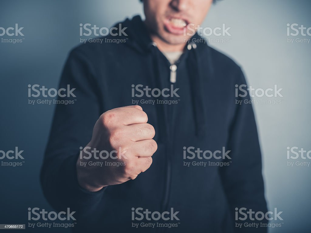 Young man raising his fist stock photo