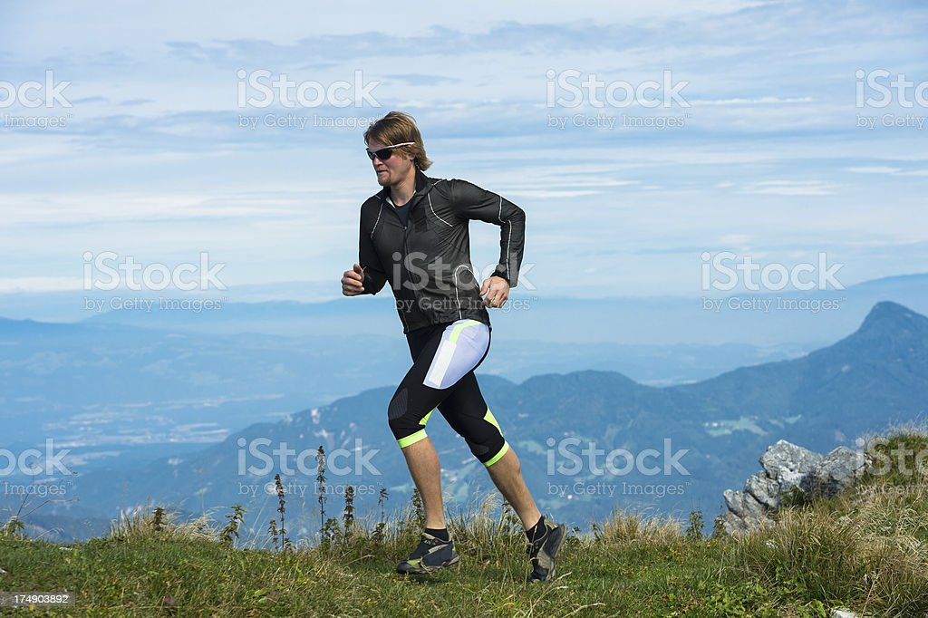 Young man reaching the mountain peak royalty-free stock photo