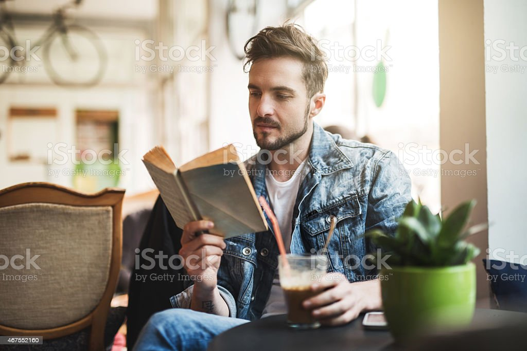 Young man reading a book in a cafe. stock photo