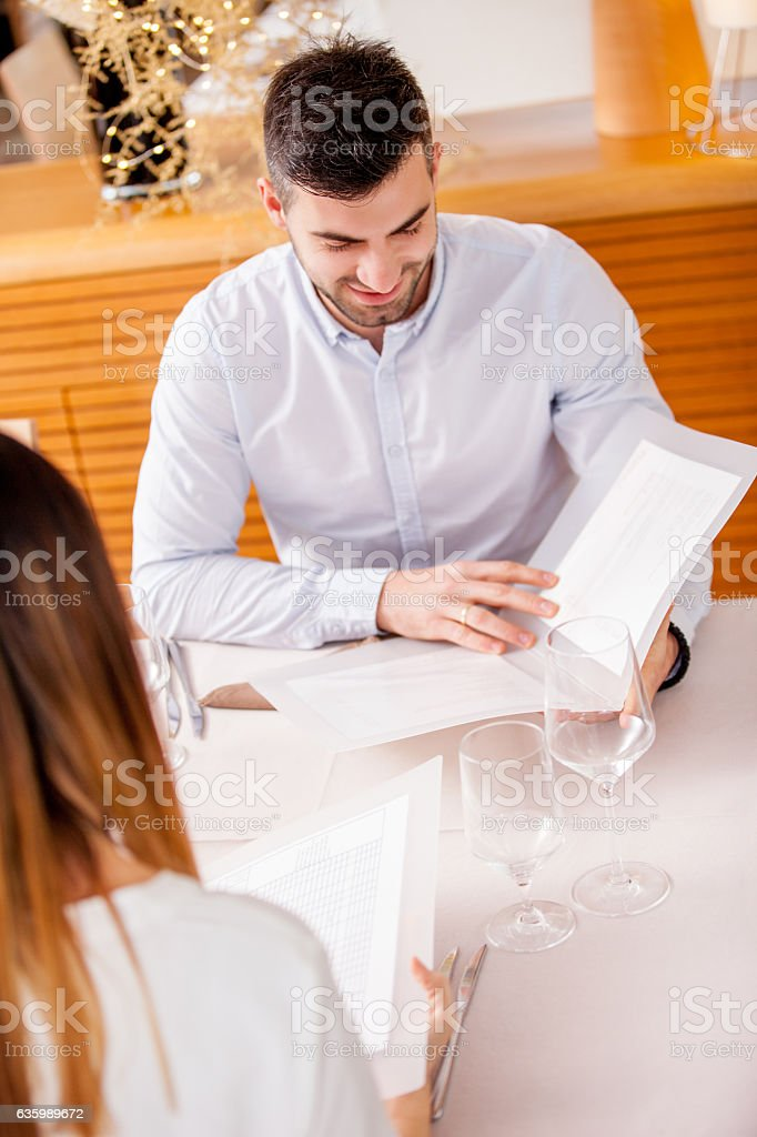 Young Man reading a Menu in a Restaruant stock photo