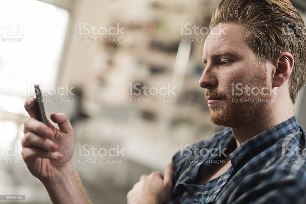 Young man reading a text message on smart phone. stock photo