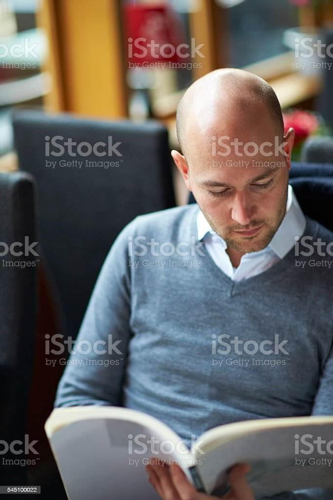 Young man reading book in cafe stock photo