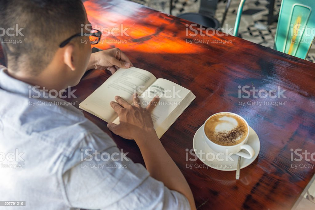 Young man reading book in the morning stock photo