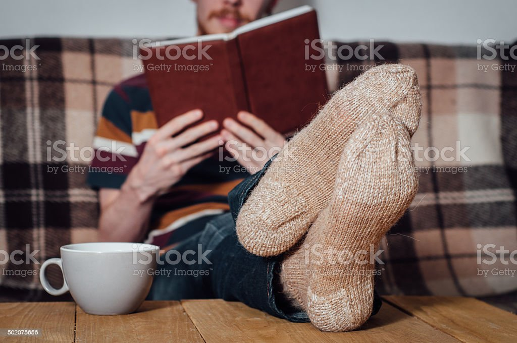 Young man reading book on coach in holey socks stock photo