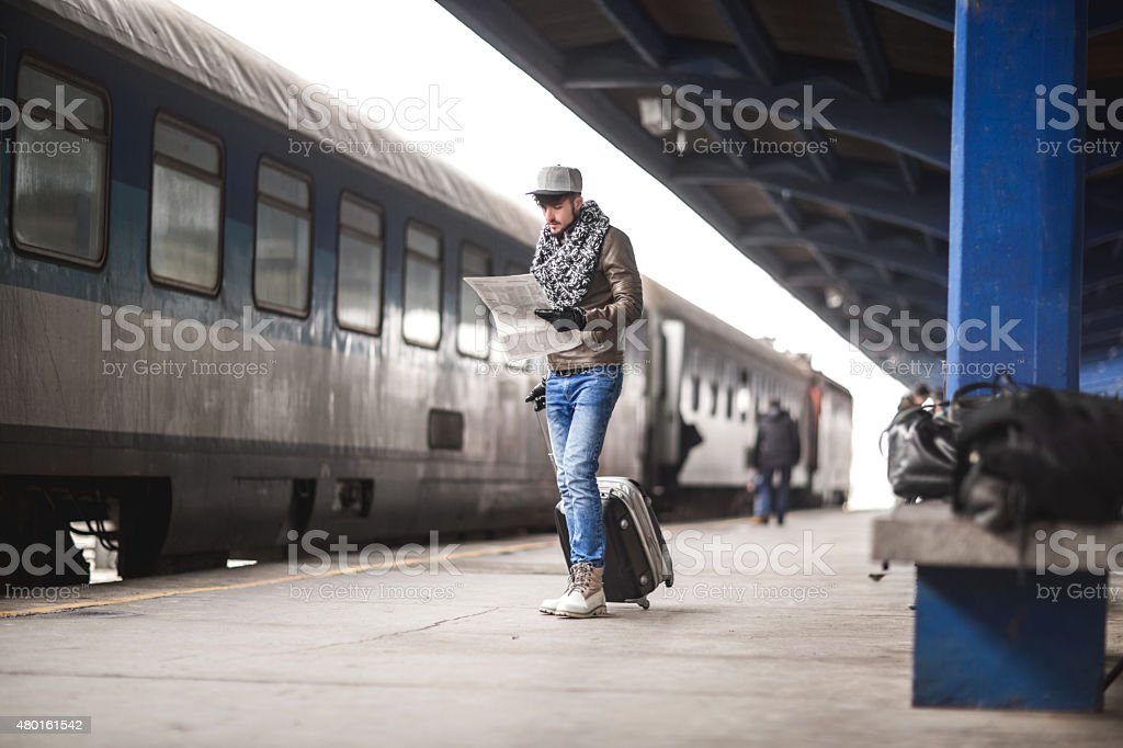 Young man reading newspapers on a train station. stock photo