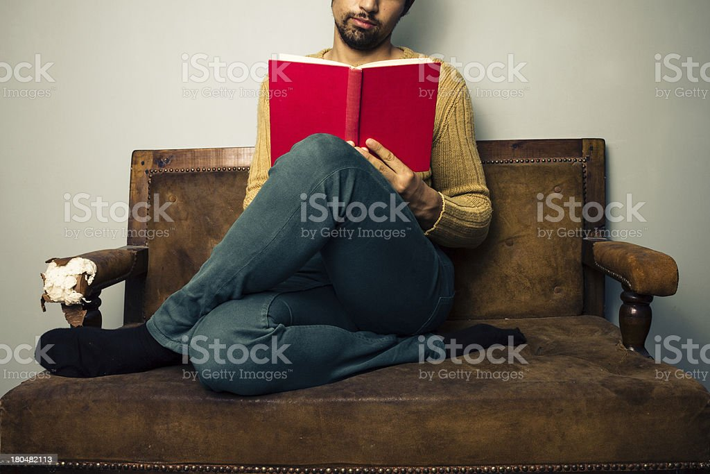 Young man reading on old sofa royalty-free stock photo