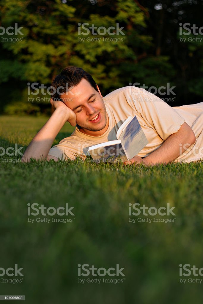 Young man reading outdoors stock photo