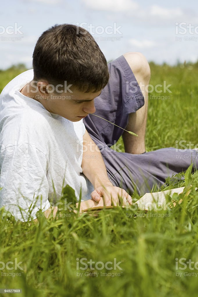 Young man reads a book. stock photo