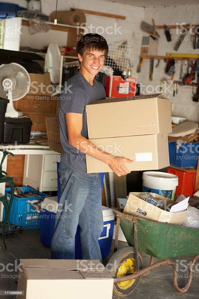 A young man rearranges the contents of his garage  royalty-free stock photo