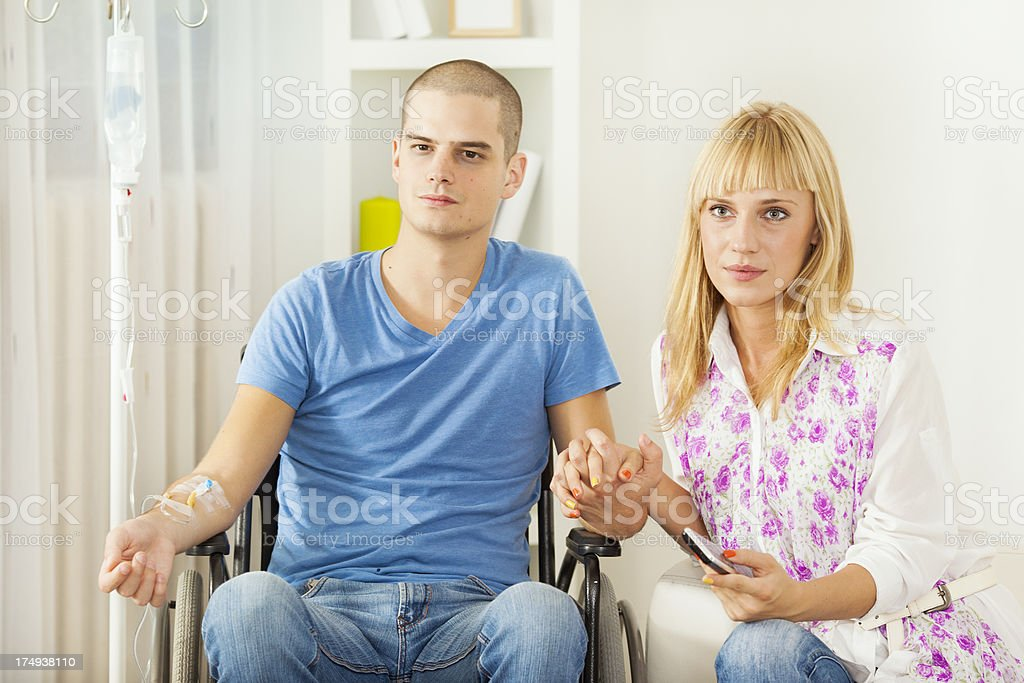 Young Man Receiving Chemotherapy with his girlfriend at home. stock photo