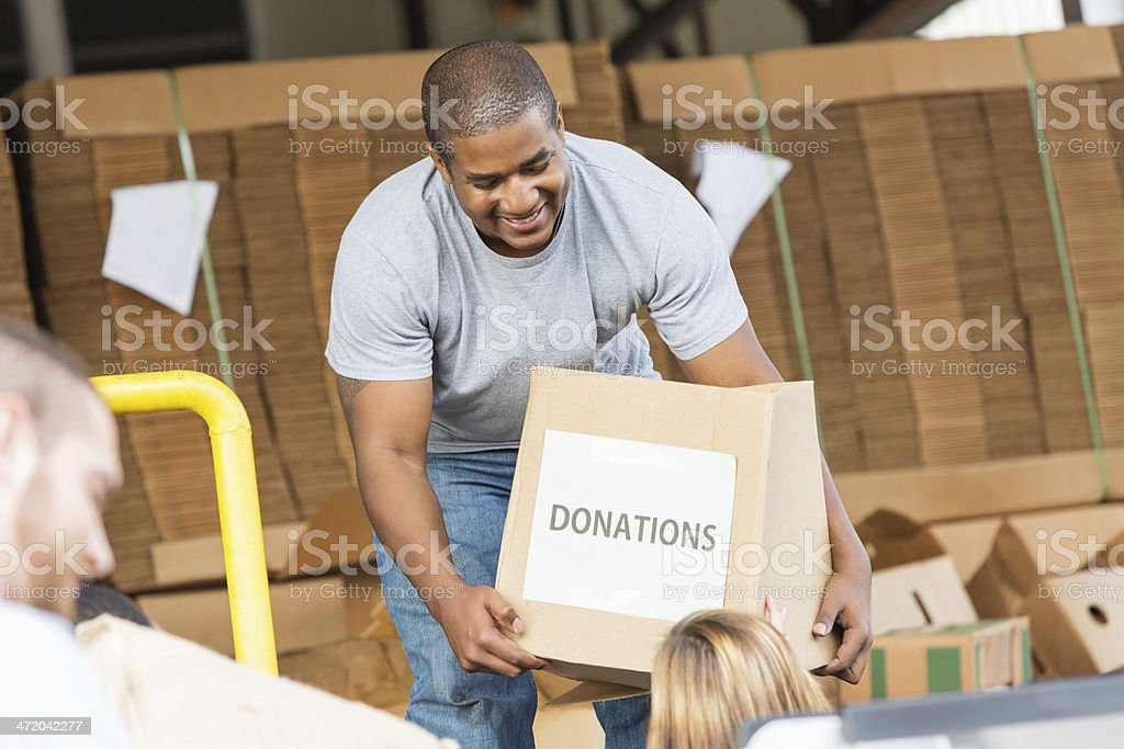 Young man receiving donations from charitable people royalty-free stock photo