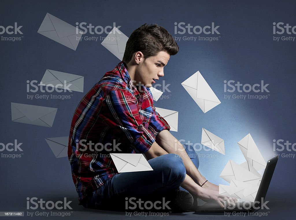 Young man receiving tons of messages on laptop stock photo