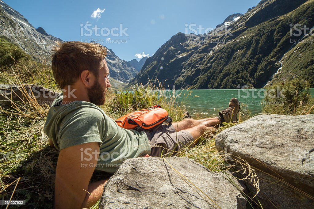 Young man relaxes at the mountain lake after long hike stock photo
