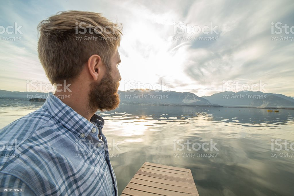 Young man relaxes on lake pier, looks at view stock photo