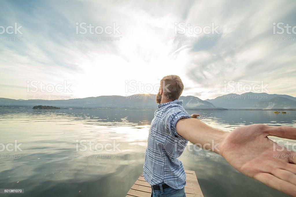Junger Mann entspannt auf See pier, steht Ausgestreckte Arme – Foto