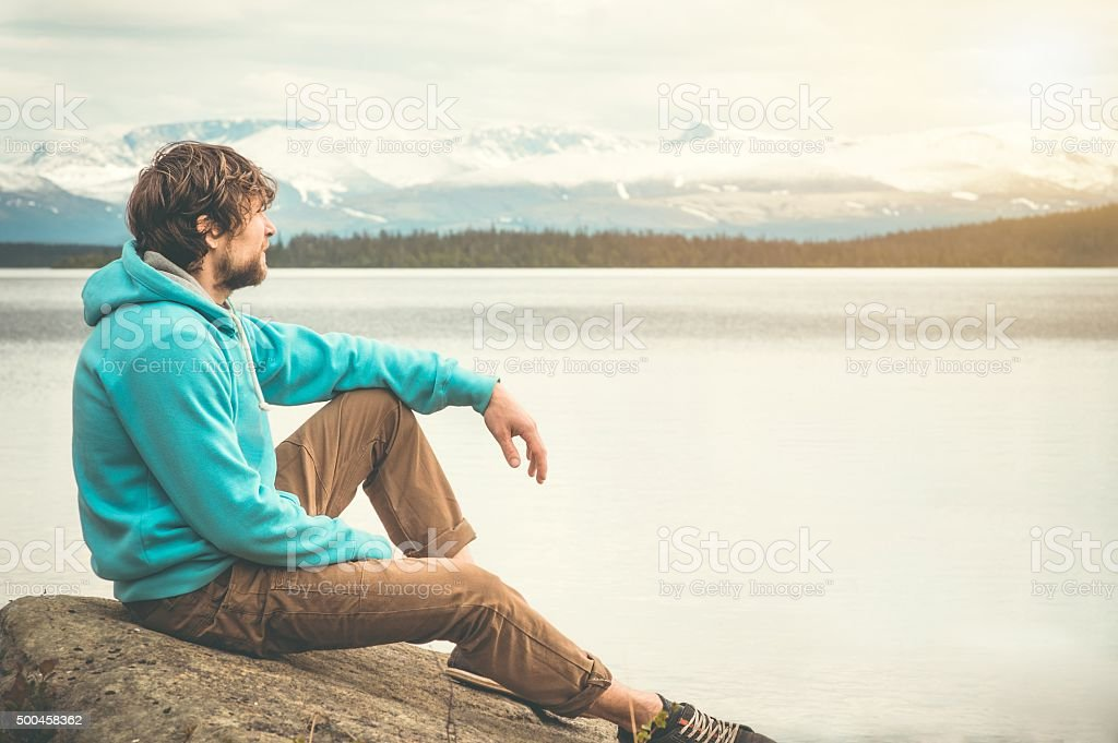 Young Man relaxing alone outdoor Lifestyle Travel concept stock photo