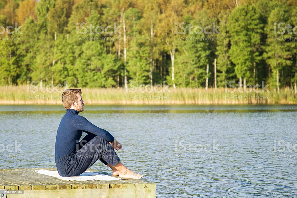 Young man relaxing and practicing yoga on the lake footbridge. stock photo