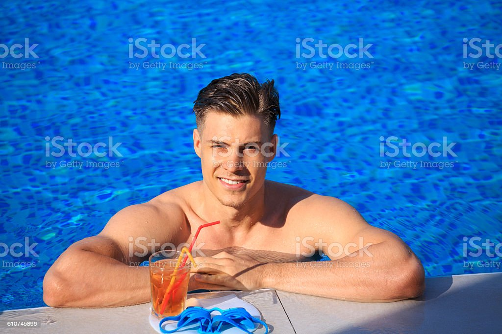 Young man relaxing at swimming pool stock photo