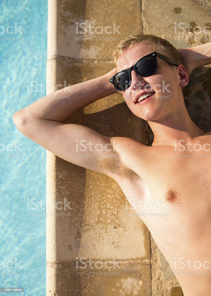 Young man relaxing by pool with sunglasses royalty-free stock photo