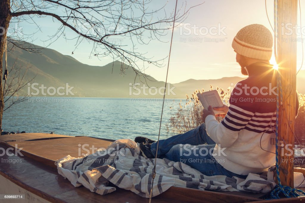 Young man relaxing by the lake, reading book stock photo