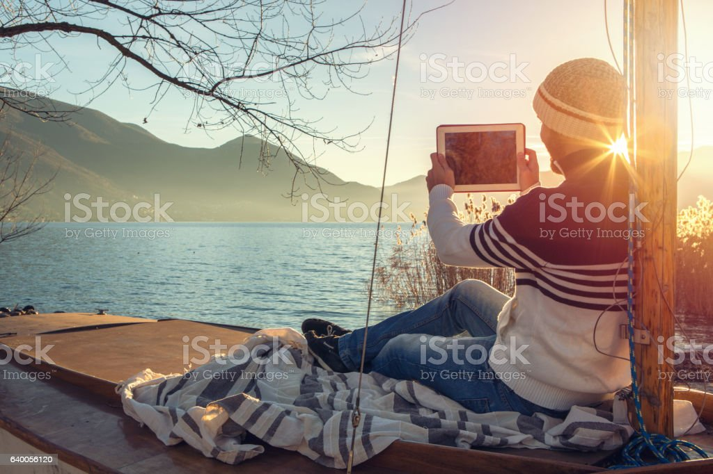 Young man relaxing by the lake, takes digital tablet picture stock photo