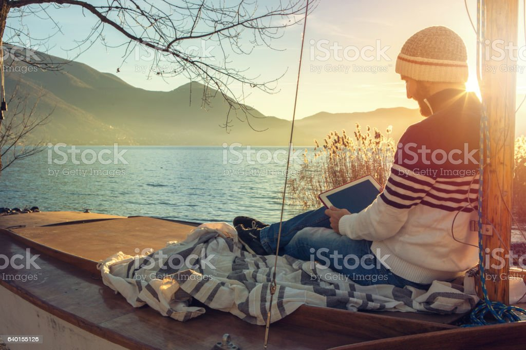 Young man relaxing by the lake with digital tablet stock photo