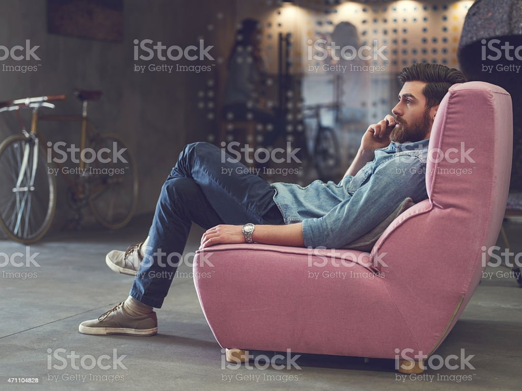 Young man relaxing in armchair and talking on the phone. stock photo