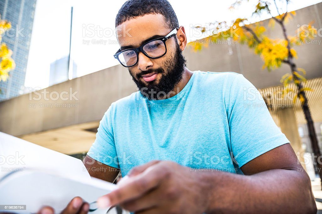 Young man relaxing in downtown reading a book stock photo