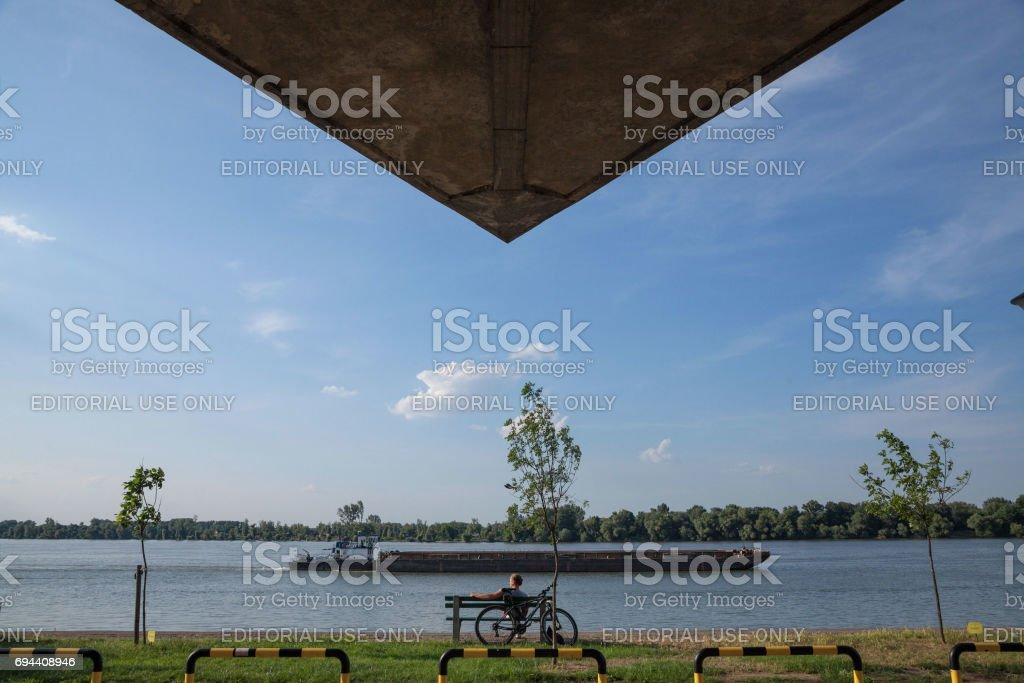 Young man relaxing in front of Danube river, in Belgrade, on Donji Dorcol district, Serbia, a barge passing by on the water stock photo