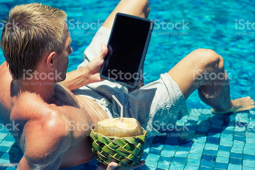 Young Man Relaxing in Pool Tablet Computer and Drinking Coconut stock photo