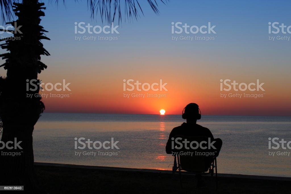 Young man relaxing in the beach on sunset stock photo