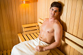Young man relaxing in the sauna