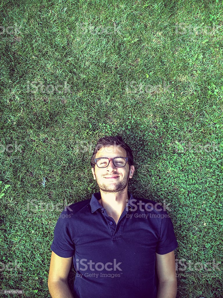 Young man relaxing outdoors stock photo