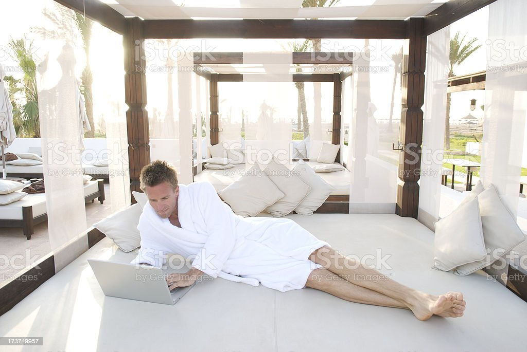 Young Man Relaxing with Laptop Computer Platform Bed Resort stock photo
