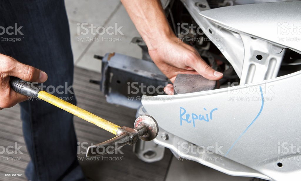 Young Man Repairing Car In Body Shop stock photo