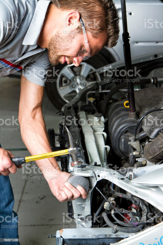 Young Man Repairing Car In Body Shop royalty-free stock photo