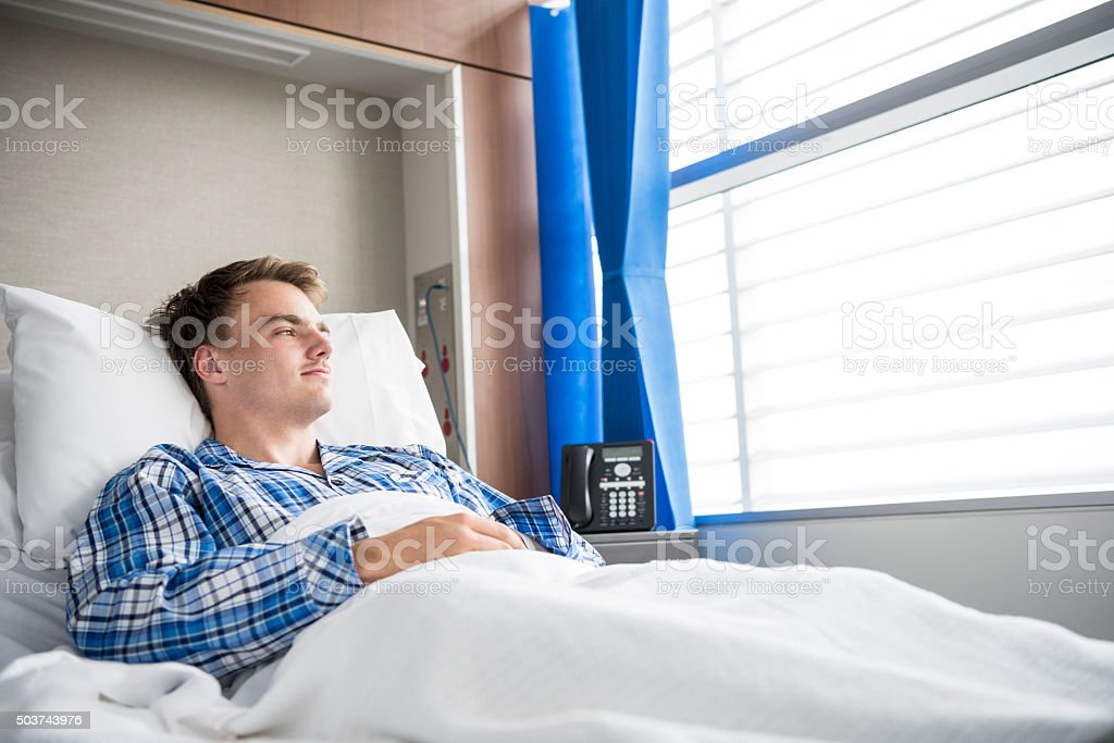 Young man resting in hospital bed looking through window stock photo