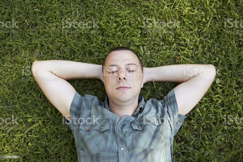 Young man resting on grass stock photo