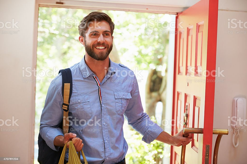 Young Man Returning Home For Work With Shopping stock photo