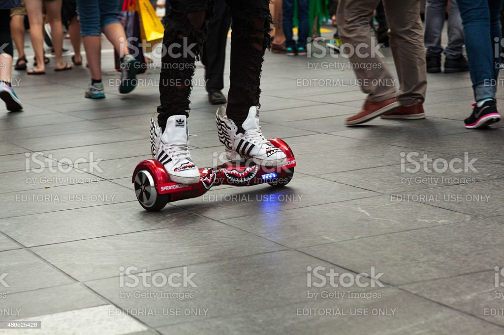 Young man ride trendy hoverboard / skateboard in Times Square NYC stock photo