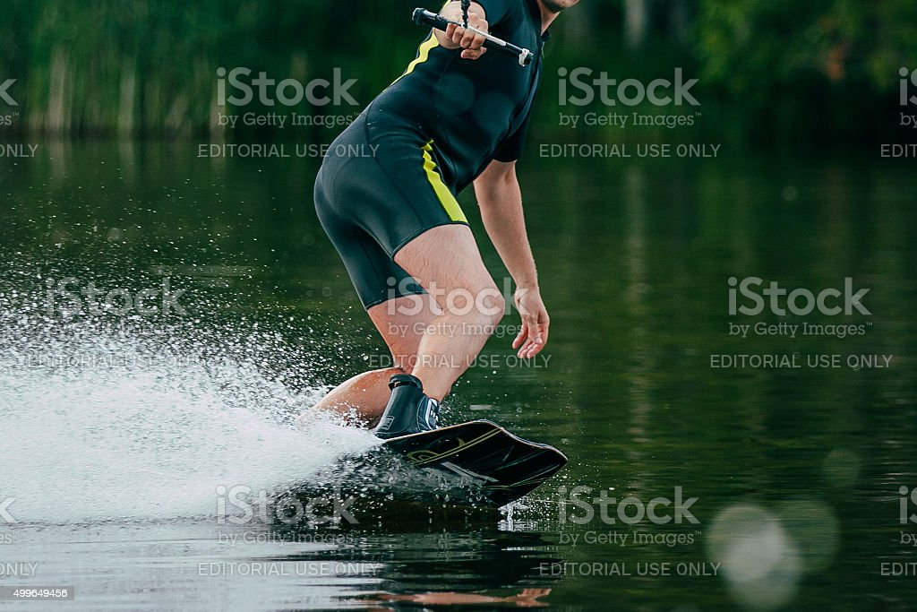 young man rides a wakeboard on lake stock photo