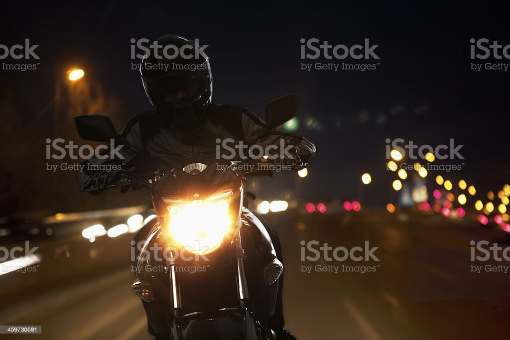 Young Man riding a motorcycle at night stock photo